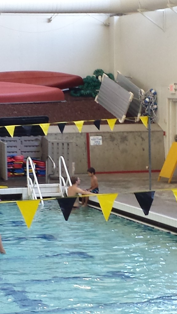A nervous Logan sits by the pool talking with his instructor.
