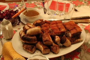 The traditional Norwegian holiday meal called ribbe is often served with Christmas sausages and sauerkraut.